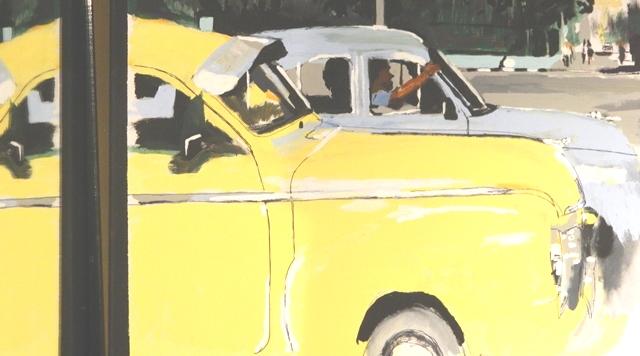 two cuban taxis cruising through havana